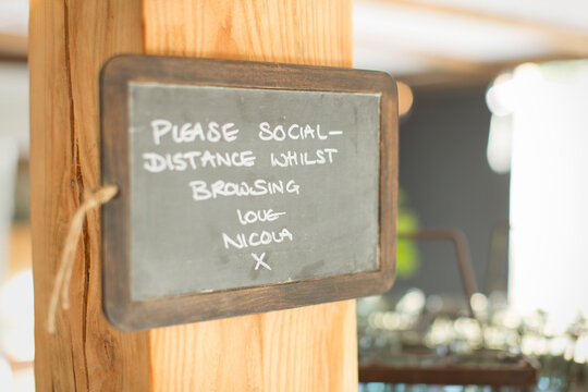 Blackboard social distancing sign in small shop