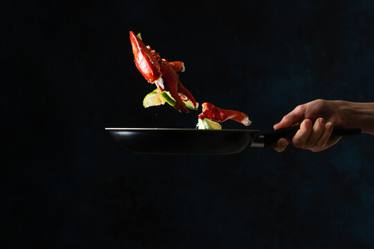 The chef toss up king crab legs with pieces of lime in a frying pan on dark blue background. Seafood concept. Frozen motion. Backstage of preparing traditional Thai dish at restaurant kitchen.