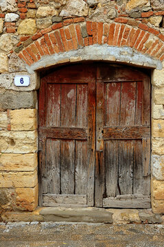 Ancient wood door on arched entry in Montereggioni, Tuscany, Italy
