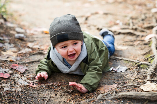 Boy hurt after falling in the forest sad and unhappy child crying