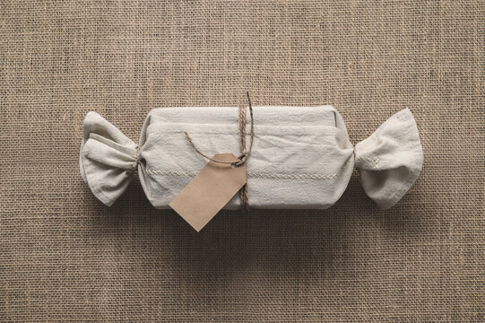 Xmas present wrapped in eco friendly natural fabric. Burlap background. Zero waste Christmas, flat lay, top view. Minimal composition