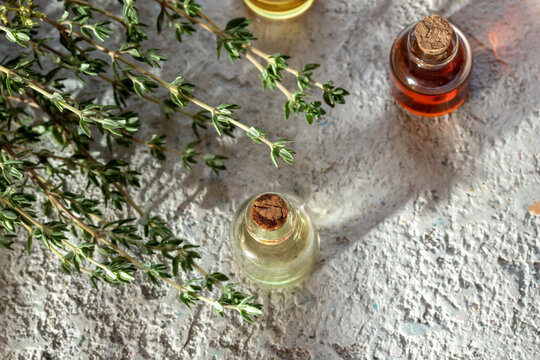 Essential oil bottles with fresh thyme, top view