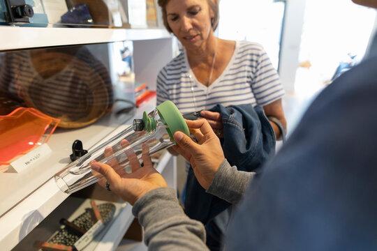 Worker showing bong to customer in marijuana dispensary