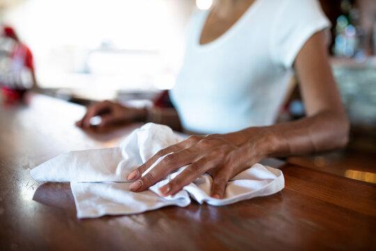 Close up waitress wiping bar with towel