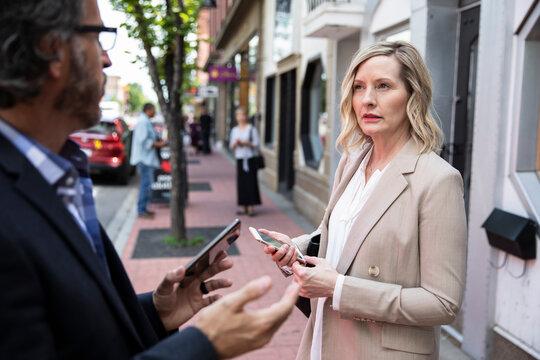 Business people with smart phones talking on city sidewalk
