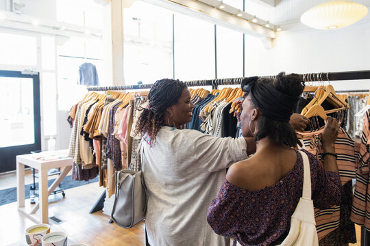 Women friends shopping for clothing at rack in boutique