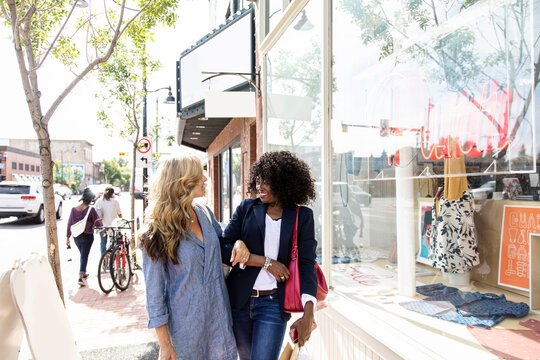 Happy woman friends walking arm in arm along sunny storefront