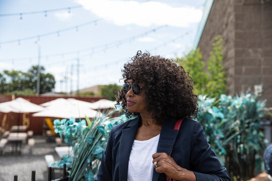 Woman in sunglasses standing at restaurant patio