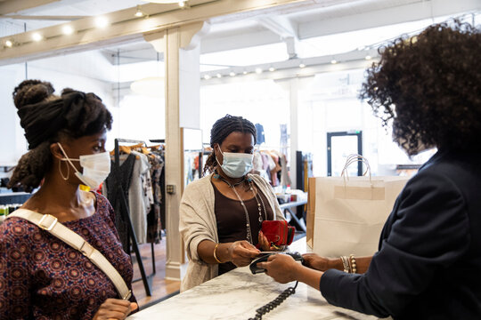 Female customers in face masks paying cashier in clothing boutique