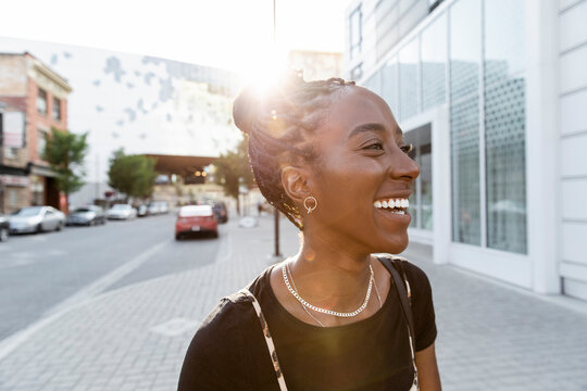 Happy young woman laughing on sunny city sidewalk