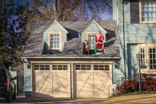 Two car garage of upscale house with plastsic santa and deer displayed by upstairs windows in evening
