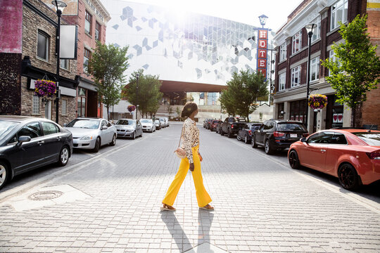 Stylish young woman crossing sunny city street
