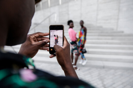 Young man with smart phone photographing stylish women on steps