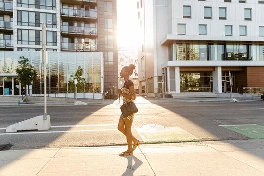 Stylish young woman walking on sunny city sidewalk