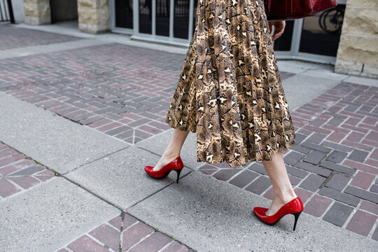 Stylish non-binary young adult walking in high heels and skirt