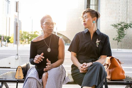 Stylish mature women friends talking on city bench