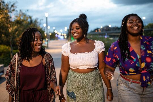 Happy young women friends walking on city sidewalk at night