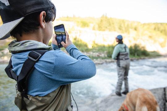 Boy taking photo of woman on fishing trip