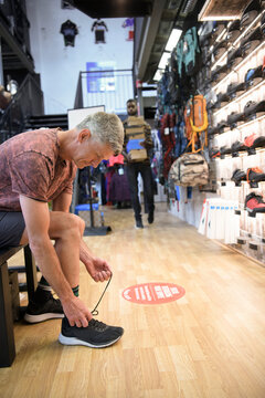 Man trying on athletic shoes in sporting goods store