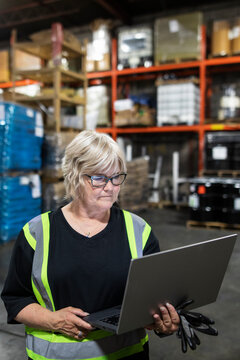 Distribution warehouse owner using laptop in middle of depot