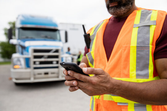 Warehouse worker texting on phone near container truck