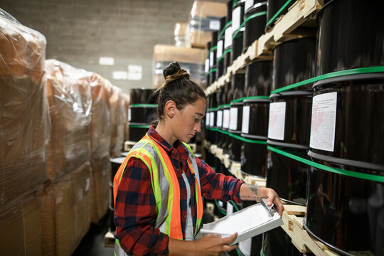 Woman checking shelves of drums in distribution warehouse