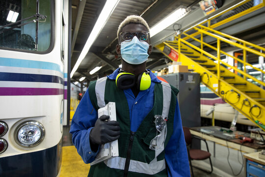 Confident male transit worker in face mask in maintenance facility