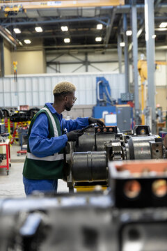 Male transit engineer inspecting parts in maintenance facility