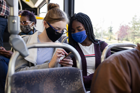 Teenage girl friends in face masks using smart phone on public bus