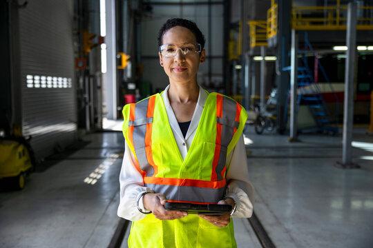 Portrait confident female transit supervisor with digital tablet