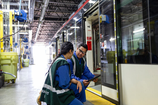 Transit workers inspecting subway in maintenance facility