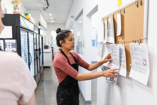 Women planning work schedule in catering kitchen