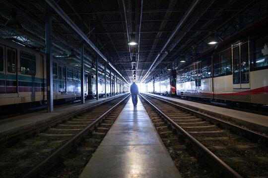 Rear view of woman walking on railway platform in subway train workshop