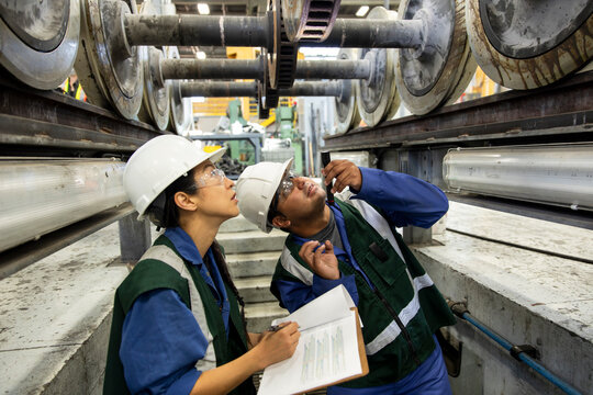 Man and woman inspecting wheel in subway train workshop