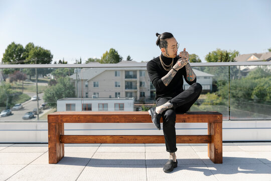 Asian man sitting on bench lighting cigarette