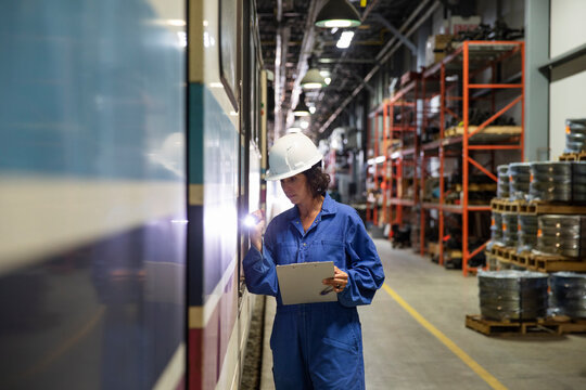 Female transit engineer with flashlight inspecting subway