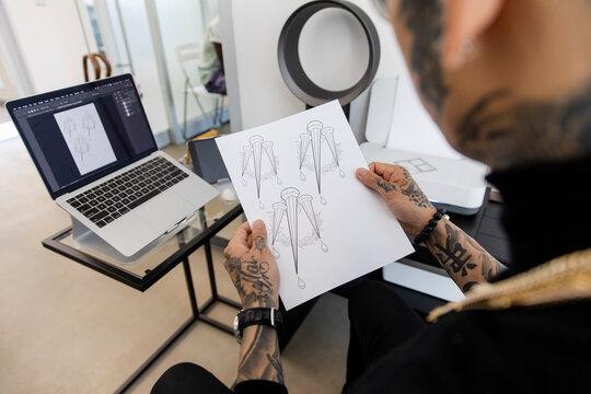 Tattoo artist looking at designs in studio
