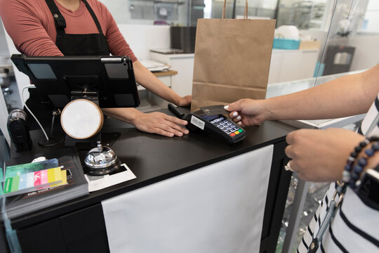 Customer paying contactlessly in cake shop