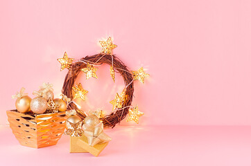 Christmas home decor in golden color - christmas wreath, glowing garland,  decorations on soft light pink background, copy space.