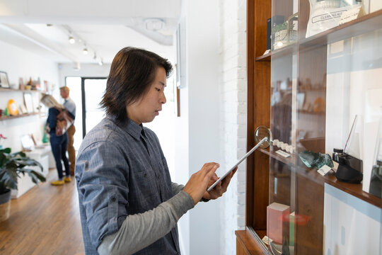 Male worker with digital tablet inventory in marijuana dispensary