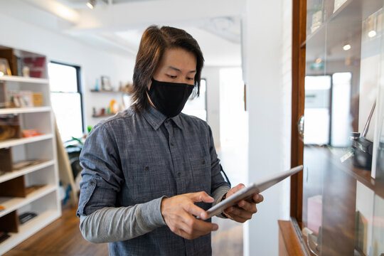Male worker in face mask using digital tablet in marijuana dispensary