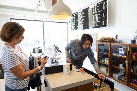 Worker helping customer in marijuana dispensary