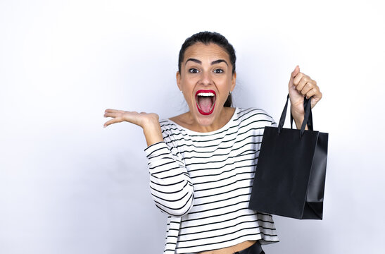 Young beautiful woman holding a black shopping bag crazy and mad shouting and yelling with aggressive expression and arms raised. Black Friday