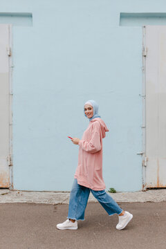 Stylish muslim woman in jeans, hoodie or longsleave, headscarf goes on the street and looks at the camera