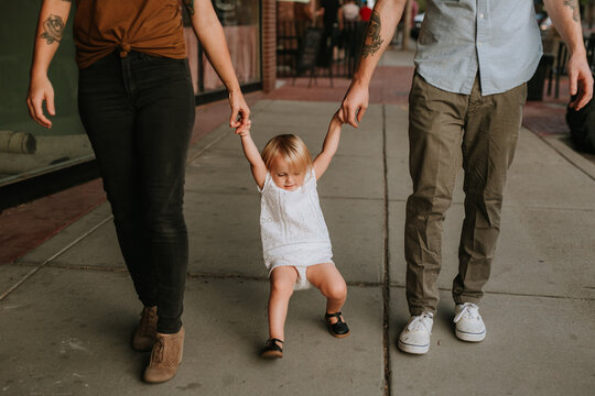 Toddler Walking Silly and Holding Parents' Hands