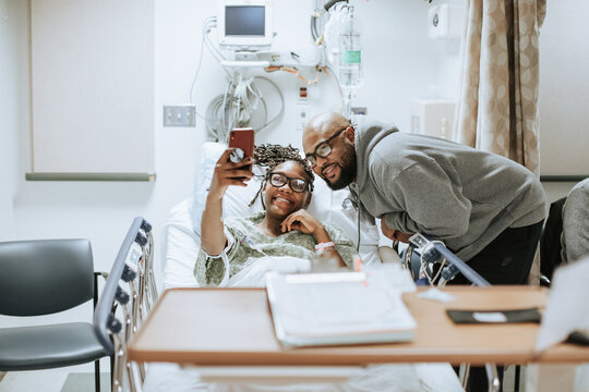 Woman Taking Selfie with Family before Surgery in Hospital Room