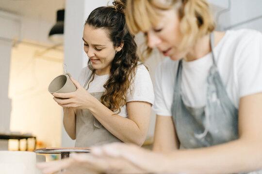 Craftswoman making crockery in studio