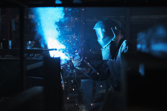 Industrial worker in protective mask using modern welding machine for welding metal construction on production manufacture at metalworking factory