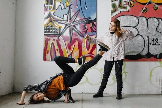 Break dancer standing on hands in art hall.