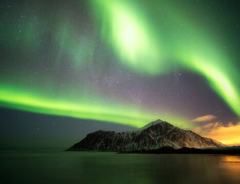 Northern lights shine in the sky above the mountain range.